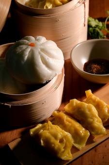 Przycięte ujęcie chińskich pierożków domowej roboty z sosem sojowym i bułką