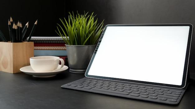 Przycięte ujęcie ciemnego nowoczesnego obszaru roboczego z tabletem z pustym ekranem, filiżanką kawy, artykułami biurowymi i dekoracjami