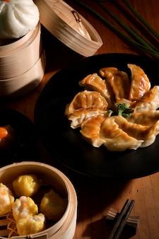 Przycięte ujęcie dim sum z gyozą i bułeczką podawane na tradycyjnym parowcu