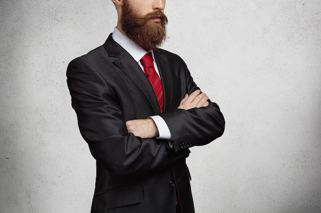 Przycięte ujęcie dobrze wyglądającego, pewnego siebie i odnoszącego sukcesy brodatego przedsiębiorcy, stojącego z założonymi rękami i myślącego o ważnej transakcji biznesowej.