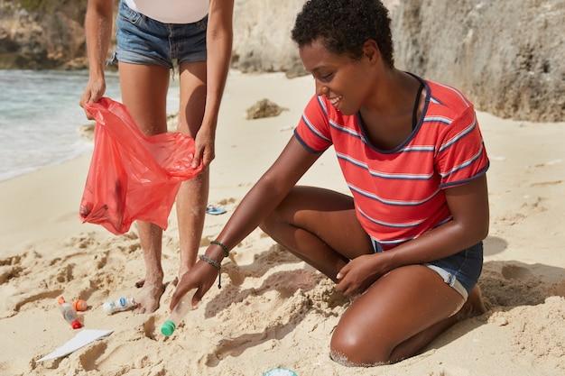 Przycięte ujęcie dwóch aktywnych międzyrasowych turystów czyszczących brudną plażę