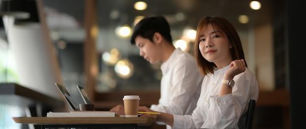 Przycięte ujęcie dwóch biznesmenów siedzących w przestrzeni coworkingowej podczas pracy nad ich projektem