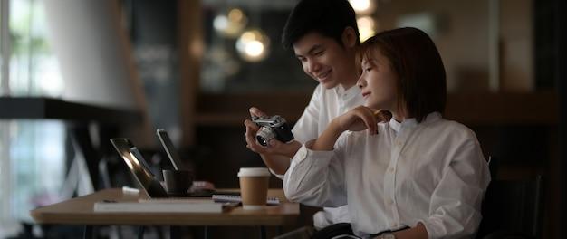 Przycięte ujęcie dwóch fotografów konsultujących ich pracę z aparatem i laptopem