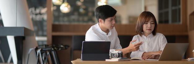 Przycięte ujęcie dwóch fotografów siedzących w przestrzeni coworkingowej i konsultujących swój projekt
