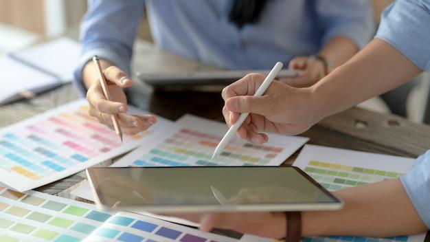 Przycięte ujęcie dwóch młodych projektantów konsultujących się w sprawie wyboru koloru na drewnianym biurku
