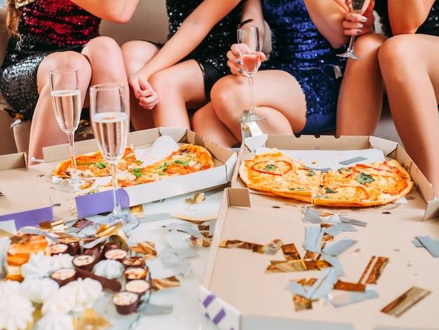 Przycięte ujęcie kobiet siedzących przed pizzą w pudełkach, talerz ze słodyczami i kieliszki z winem musującym.