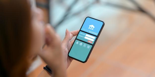 Przycięte ujęcie kobiety robi bankowości internetowej na smartfonie w wygodnym miejscu pracy