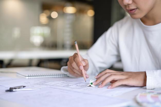Przycięte ujęcie kreatywnego architekta projektującego i szkicującego projekt budowlany w miejscu pracy.