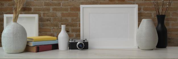 Przycięte ujęcie marmurowego blatu ozdobionego ramkami, wazami ceramicznymi, aparatem i książkami