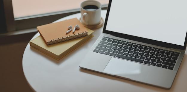 Przycięte ujęcie minimalnego miejsca pracy z laptopem z notebookiem i materiałami biurowymi
