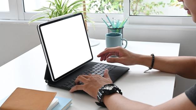 Przycięte ujęcie młodego mężczyzny przeglądającego internet lub łączącego się z siecią bezprzewodową za pomocą tabletu w biurze.