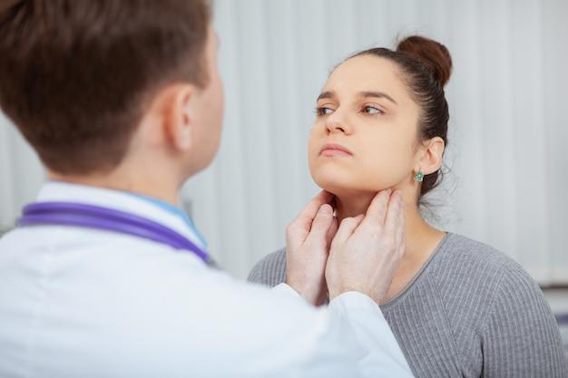 Przycięte ujęcie młodej kobiety, której szyja i gardło badane są przez lekarza w szpitalu.