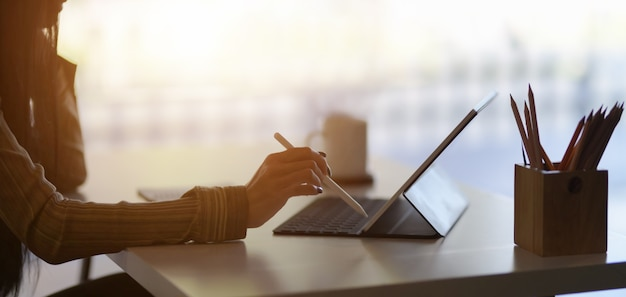 Przycięte ujęcie młodej projektantki opracowującej swój projekt za pomocą cyfrowego tabletu w nowoczesnym biurze