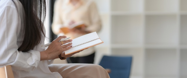 Przycięte ujęcie młodej studentki czytania jej wykładu na swoim notatniku