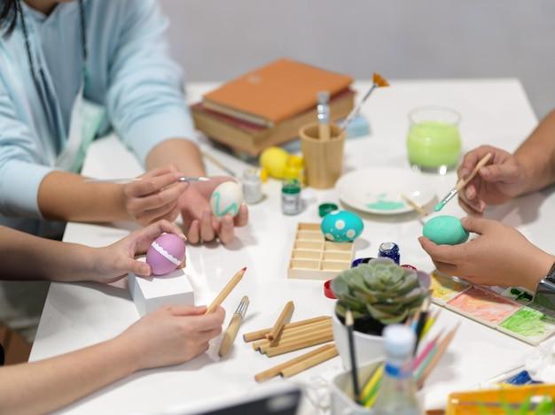 Przycięte ujęcie nastolatków rąk malujących pisanki, przygotowujących się do festiwalu wielkanocnego przy użyciu narzędzi do malowania
