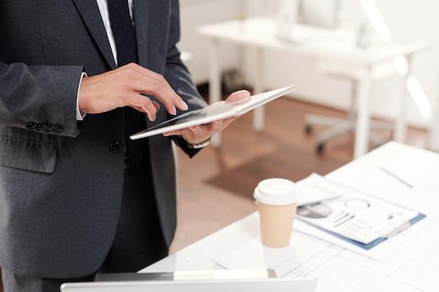 Przycięte ujęcie nierozpoznawalnego biznesmena odnoszącego sukcesy trzymającego cyfrowy tablet nad miejscem pracy