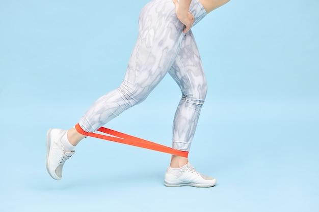 Przycięte ujęcie nierozpoznawalnej sportsmenki w legginsach i trampkach ćwiczących z opaską, aby uzyskać idealne pośladki, nogi treningowe, pracę nad mięśniami, wzmocnienie pośladków i ścięgien podkolanowych