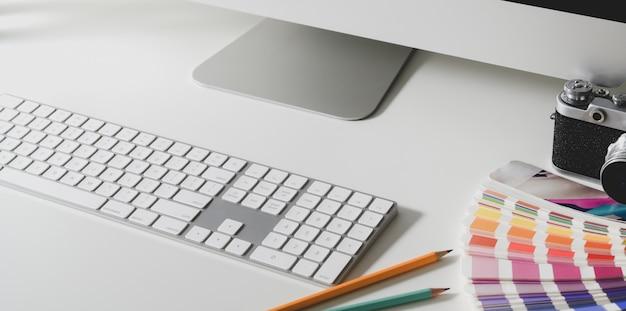 Przycięte ujęcie nowoczesnego obszaru roboczego projektanta z komputerem z klawiaturą i próbkami kolorów
