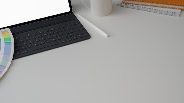 Przycięte ujęcie obszaru roboczego projektanta z tabletem, materiałami projektowymi i przestrzenią do kopiowania