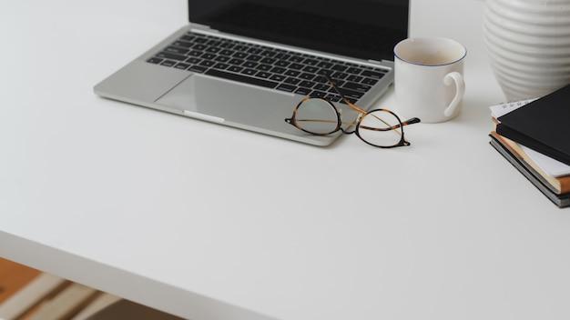 Przycięte ujęcie obszaru roboczego z laptopem, materiały biurowe, filiżanka kawy i kopia miejsce na białym biurku