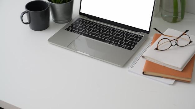 Przycięte ujęcie obszaru roboczego z pustym ekranem laptopa, miejsca kopiowania, materiałów biurowych i filiżanki kawy na białym biurku
