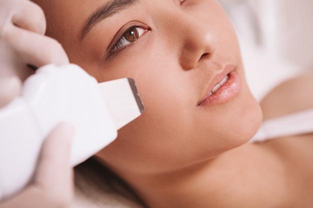 Przycięte ujęcie pięknej azjatyckiej kobiety podczas zabiegu kawitacji ultradźwiękowej w klinice urody