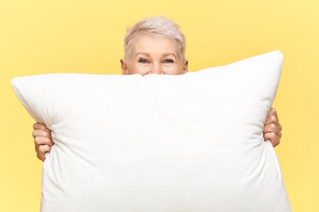 Przycięte ujęcie pięknej kobiety w średnim wieku z krótkimi włosami ukrywającej się za białą dużą poduszką z piórami z miejscem na kopię
