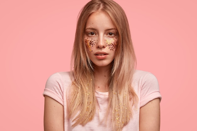 Przycięte ujęcie pięknej młodej kobiety o jasnych włosach, zdrowej skórze, błyszczy na policzkach, ozdobiona twarz, przygotowuje się do świątecznego wydarzenia, ubrana w swobodną koszulkę, stoi przy różowej ścianie
