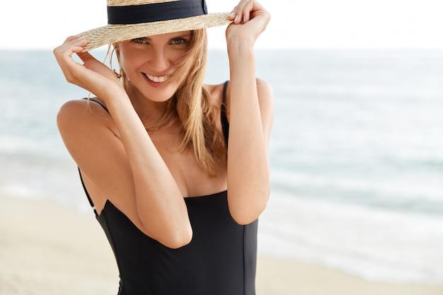 Przycięte ujęcie pięknej młodej kobiety z przyjemnym uśmiechem na tle widoku na ocean, ma radosny wygląd, nosi czarne bikini, lubi letni wypoczynek w tropikalnym kraju. ludzie, koncepcja odpoczynku