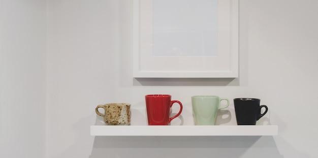 Przycięte ujęcie półki ściennej z filiżankami kawy i makiety ramy