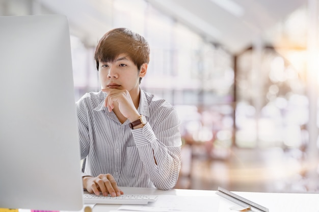 Przycięte ujęcie poważnego azjatyckiego biznesmena myślącego i koncentrującego się na pisaniu na laptopie w przestrzeniach współpracujących. koncepcja pracy laptopa człowieka