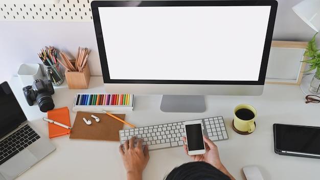 Przycięte ujęcie pracy biurka, podczas gdy biznesmen pisze i pokazuje telefon komórkowy przed białym pustym ekranem komputera.