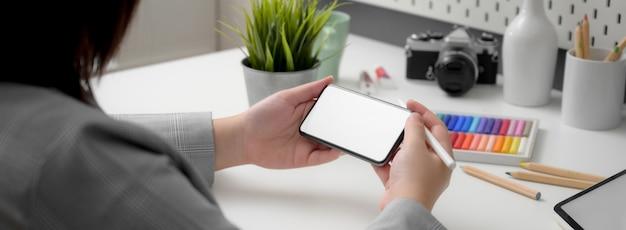 Przycięte ujęcie profesjonalnego projektanta za pomocą poziomego makiety smartfona