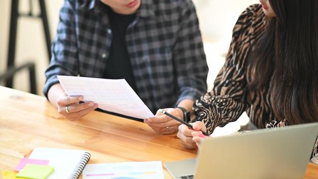 Przycięte ujęcie projekt graficzny, spotykają projekt na stole z laptopem.