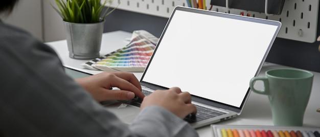 Przycięte ujęcie projektanta pracującego nad makietą laptopa, materiałami projektowymi i filiżanką kawy