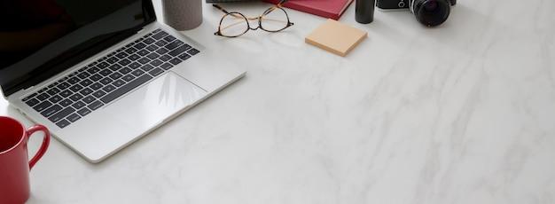 Przycięte ujęcie prostego obszaru roboczego z laptopem, filiżanką kawy, materiałami eksploatacyjnymi i kopią miejsca na marmurowym biurku