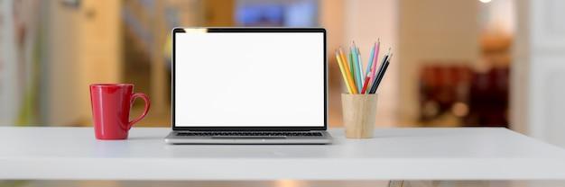 Przycięte ujęcie prostego obszaru roboczego z pustym ekranem laptopa, czerwonego kubka, materiałów biurowych i przestrzeni kopii