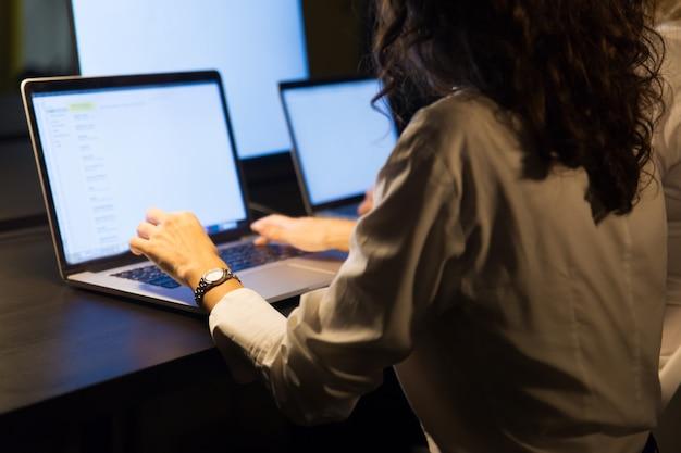 Przycięte ujęcie przedsiębiorców pracujących z laptopami