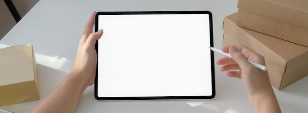 Przycięte ujęcie przedsiębiorców rozpoczynających pracę z tabletem i pudełkami