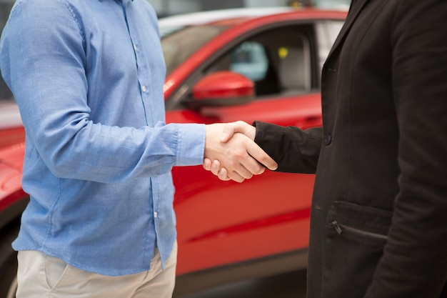 Przycięte ujęcie przedstawiające dealera samochodowego, ściskającego dłoń swojemu klientowi po sfinalizowaniu transakcji.
