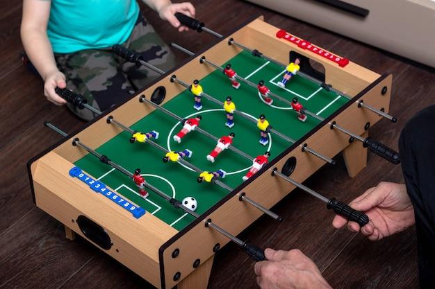 Przycięte ujęcie przedstawiające mecz piłkarzyków, w który gra mały chłopiec z ojcem. piłkarzyki to zabawka dla dzieci i dorosłych