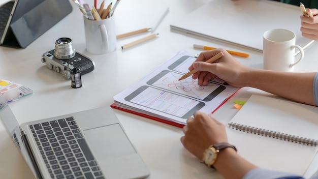 Przycięte ujęcie przedstawiające projektantów aplikacji na smartfony opracowują nowe projekty, aby pokazać je klientom.