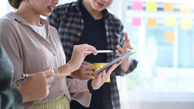 Przycięte ujęcie przedstawiające zespół kreatywnych projektantów korzystający z cyfrowego tabletu i spotykający się w biurze kreatywnym.