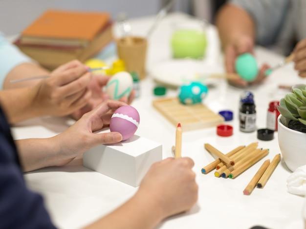 Przycięte ujęcie rąk malujących pisanki, przygotowujących się do festiwalu wielkanocnego z narzędziami do malowania na stole