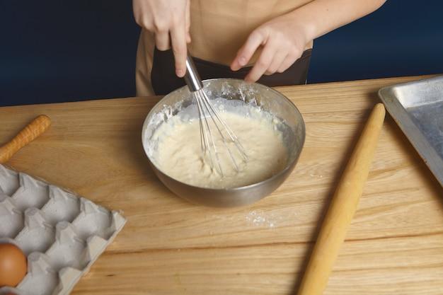 Przycięte ujęcie rąk trzymających trzepak podczas ubijania jajek mąką na ciastka sosnowe w metalowej misce.