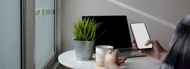 Przycięte ujęcie relaksującego żeńskiego freelancera z makiety smartfonem w przenośnym miejscu pracy