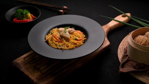 Przycięte ujęcie schezwan noodles lub chow mein z sosem warzywnym, kurczakiem i chili