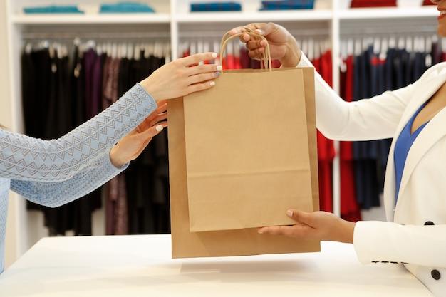Przycięte ujęcie sprzedawcy przekazującego torby na zakupy klientowi płci żeńskiej