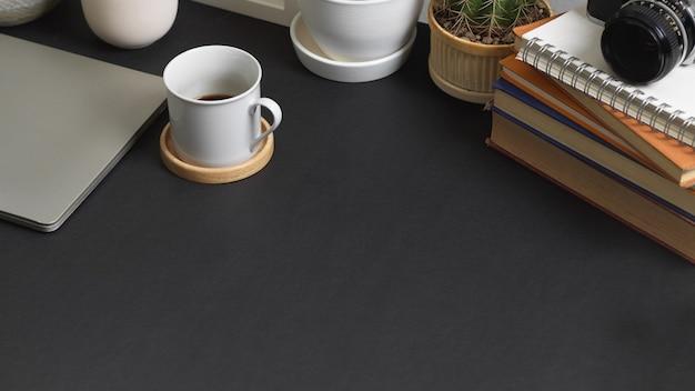 Przycięte ujęcie stołu roboczego z miejscem na kopię, kubkiem kawy, materiałami eksploatacyjnymi i książkami w pokoju biurowym w domu