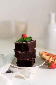 Przycięte ujęcie stosu czekoladowe ciasteczka na białym talerzu z liściem mięty i truskawką na wierzchu